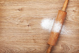 Rolling pin with flour on wooden table