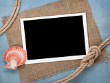 Blank photo frame with seashell and ship rope
