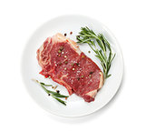 Raw sirloin steak with rosemary and spices on plate