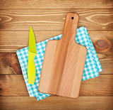 Cutting board and knife over kitchen towel