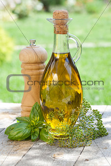 Olive oil bottle, pepper shaker and herbs