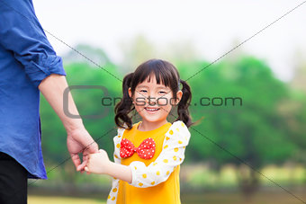 cute girl hold father hand in the park