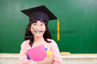 smiling girl wear a graduation hat and holding books