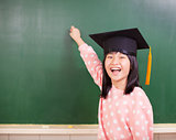 happy little girl wear a graduation hat with blackboard