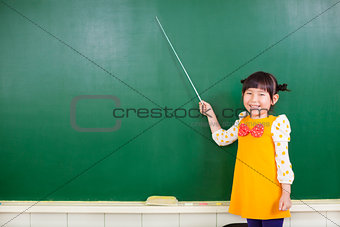 asian little girl using a baton to point on a blackboard