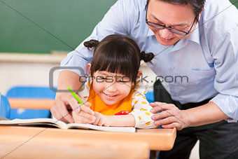 Teacher teaches a student to using a pencil