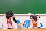 two sad girls doing in homework