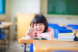 happy kid thumb up with book in class