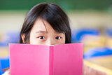 girl uses a book to cover her face
