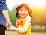 pretty girl hold father hand  in the park with sunlight