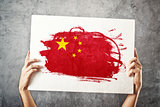 China flag. Man holding banner with Chinese Flag.