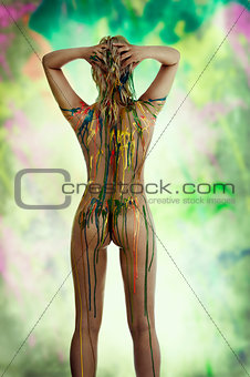 blond nude girl with multicolor over her body posing from back v