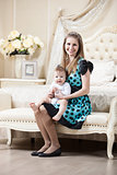 Young Caucasian woman posing with little son while sitting on couch in bedroom