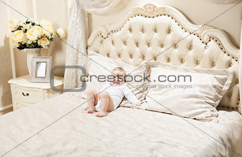 Little boy lying on bed at home and smiling