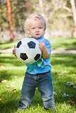 Young Cute Boy Playing with Soccer Ball in Park