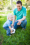 Young Boy and Dad Playing with Soccer Ball in Park