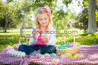 Cute Young Girl Coloring Her Easter Eggs with Paint Brush