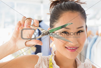 Beautiful female fashion designer holding scissors