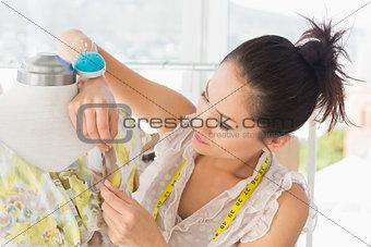 Beautiful female fashion designer working on dress