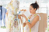 Beautiful female fashion designer working on dress