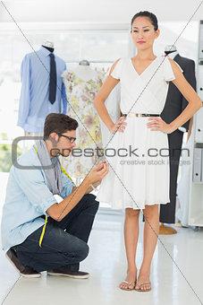 Fashion designer adjusting dress on model