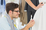Male fashion designer adjusting dress on model