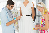 Fashion designers adjusting dress on model
