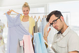 Bored man with shopping bags while woman at clothes rack