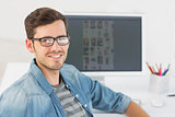 Casual male photo editor in front of computer
