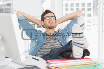 Casual young man with legs on desk in office