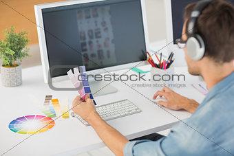 Casual male photo editor using computer