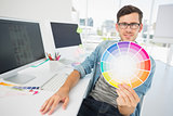 Male artist holding color wheel at desk
