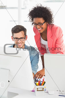 Smiling casual couple working on computer