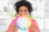 Beautiful young woman holding color wheel