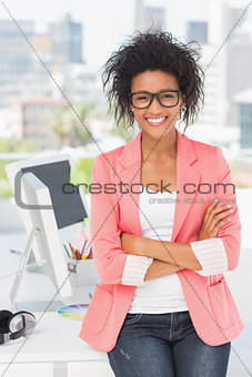 Casual female artist with arms crossed at office