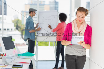 Artist using digital tablet with colleagues in background at office