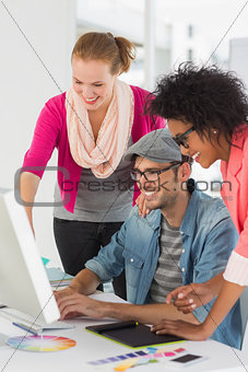 Smiling artists working on computer at office