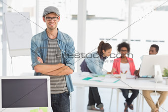 Casual male artist with colleagues in background at office