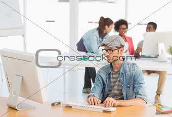 Male artist using computer with colleagues in at office