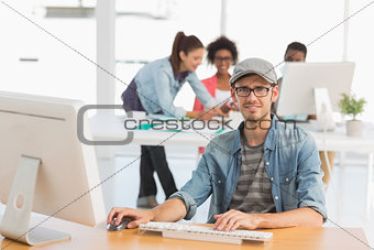 Casual male artist using computer with colleagues in background