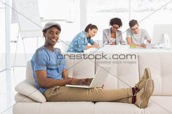 Man using laptop with colleagues in background at creative office
