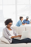 Woman using laptop with colleagues in background at creative office