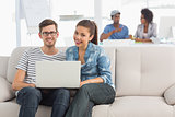 Couple using laptop with colleagues in background at creative office