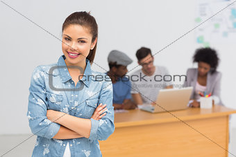 Casual female artist with colleagues in background at office