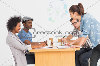 Group of artists in discussion at desk at office