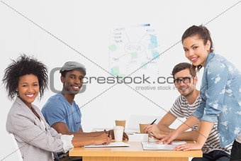 Side view of a group of artists in discussion at desk