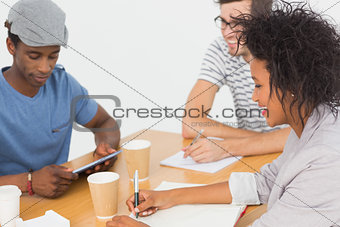Group of happy artists in discussion at desk