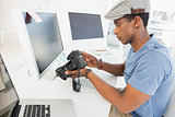 Photo editor looking at digital camera in office