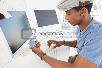 Casual young man doing online shopping in office