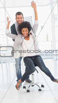 Playful man pushing woman on chair in office